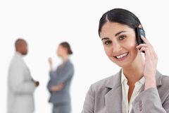 Smiling businesswoman with cellphone and co-workers behind her Royalty Free Stock Photo