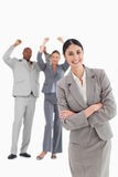 Smiling businesswoman with cheering colleagues behind her Stock Photography