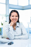 Smiling businesswoman with chin on fist Royalty Free Stock Image