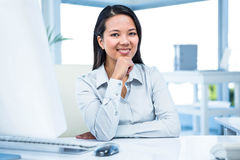 Smiling businesswoman with chin on fist Royalty Free Stock Photography