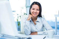 Smiling businesswoman with chin on fist Stock Photo
