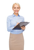 Smiling businesswoman with clipboard and pen Stock Photography