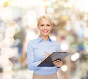 Smiling businesswoman with clipboard and pen Royalty Free Stock Images