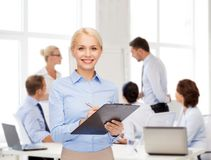 Smiling businesswoman with clipboard and pen Stock Photo