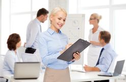 Smiling businesswoman with clipboard and pen Royalty Free Stock Photo