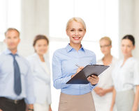Smiling businesswoman with clipboard and pen Stock Images