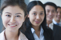 Smiling Businesswoman with co-workers portrait Stock Photography