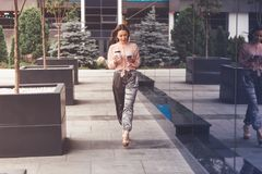 Smiling businesswoman with coffee cup walking on the street and making a phone call Royalty Free Stock Photos