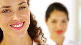 Smiling businesswoman with colleague behind her