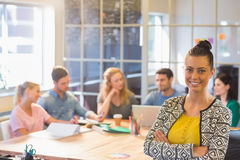 Smiling businesswoman with colleagues in background at office Stock Photo