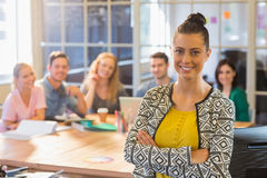 Smiling businesswoman with colleagues in background at office Royalty Free Stock Photo