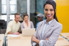 Smiling businesswoman with colleagues in office Stock Photos