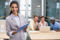 Smiling businesswoman with colleagues in office Royalty Free Stock Photos