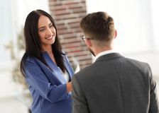 Smiling businesswoman communicating with male colleague in the o. Business couple talking in office Stock Photography