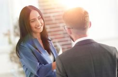 Smiling businesswoman communicating with male colleague in the o. Business couple talking in office Royalty Free Stock Photography