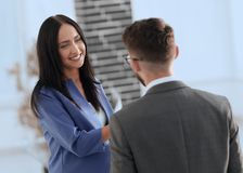 Smiling businesswoman communicating with male colleague in the o. Business couple talking in office Royalty Free Stock Photo