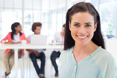 Smiling businesswoman with coworkers in background Royalty Free Stock Photo
