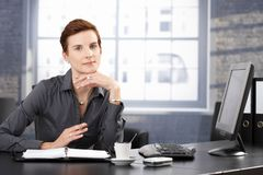 Smiling businesswoman at desk Stock Photos