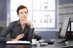 Smiling businesswoman at desk Stock Photos