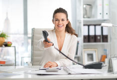 Smiling businesswoman at desk handing telephone over Royalty Free Stock Image