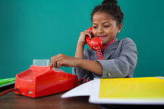 Smiling businesswoman dialing numbers on land line phone. While sitting at desk against blue background Royalty Free Stock Photos