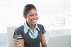 Smiling businesswoman doing online shopping Stock Image