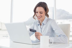 Smiling businesswoman doing online shopping in office Stock Photo