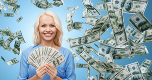 Smiling businesswoman with dollar cash money. Business, money, finance, people and banking concept - smiling businesswoman with dollar cash money over blue Stock Images