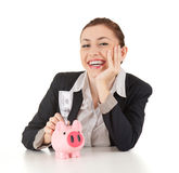 Smiling businesswoman with dollars in piggybank Royalty Free Stock Photo