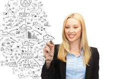 Smiling businesswoman drawing big plan in the air Royalty Free Stock Photography