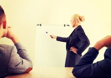 Smiling businesswoman drawing a graph for her colleagues on the whiteboard royalty free stock photo