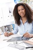 Smiling businesswoman with drawing pad. Smiling young businesswoman using drawing pad at desk Royalty Free Stock Photography
