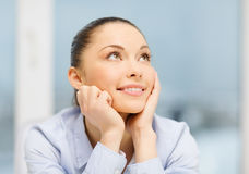 Smiling businesswoman dreaming in office Royalty Free Stock Photography