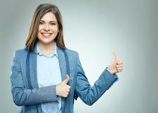 Smiling businesswoman dressed business suit shows thumbs up. Royalty Free Stock Photos