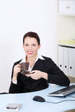 Smiling businesswoman drinking coffee. Royalty Free Stock Photos