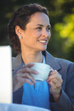 Smiling businesswoman drinking coffee with laptop Royalty Free Stock Images