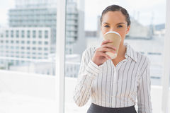 Smiling businesswoman drinking coffee while looking at camera Stock Photos