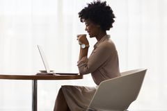 Smiling businesswoman drinking coffee and using laptop stock image