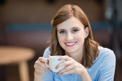 Smiling businesswoman drinking cup of coffee in office cafeteria Stock Photo
