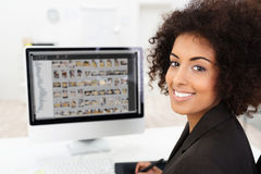 Smiling businesswoman editing photographs Stock Images