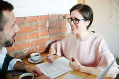 Smiling Businesswoman Explaining Contract Documents to Client in Royalty Free Stock Images