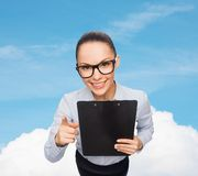 Smiling businesswoman in eyeglasses with clipboard Royalty Free Stock Images