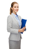 Smiling businesswoman with folder stock photography