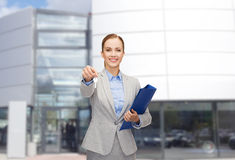 Smiling businesswoman with folder and keys Stock Photo