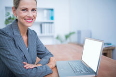 Smiling businesswoman in front of her laptop Royalty Free Stock Images