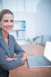 Smiling businesswoman in front of her laptop Stock Images