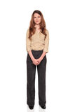Smiling businesswoman - front view full length. Isolated full length studio shot of a Caucasian businesswoman smiling and looking at the camera with her hands Stock Image