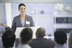 Smiling businesswoman gesturing while her colleagues watch her Royalty Free Stock Photo