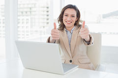 Smiling businesswoman gesturing thumbs up with laptop in office Stock Images