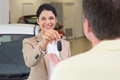 Smiling businesswoman giving car key to happy customer. At new car showroom Royalty Free Stock Image